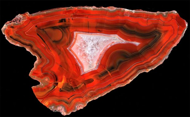 A large, bright red, banded agate in the shape of an arrowhead.