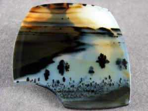 An agate that looks like a river with little trees.