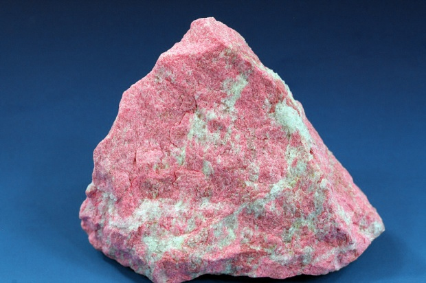 A roughly triangular chunk of rock covered with bubblegum-pink splotches.  They sparkle slightly against the contrasting blue background.