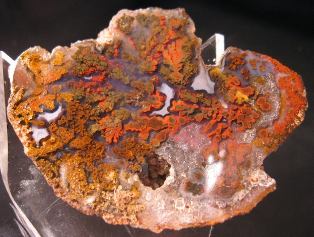 Light red translucent agate with red and orange puffy plumes appearing to float inside it.
