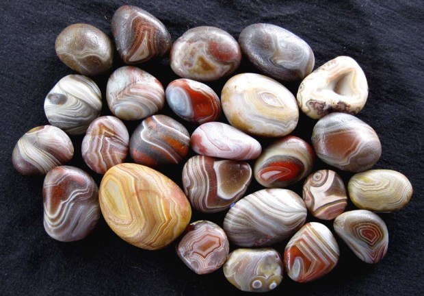 Smooth, round pebbles with bands of red, brown, gray, orange, yellow, and white.