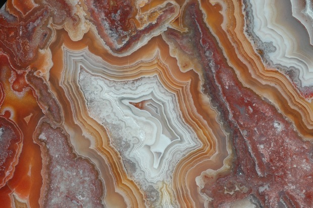 Red, orange, and white layers in a crazy lace pattern on an agate.