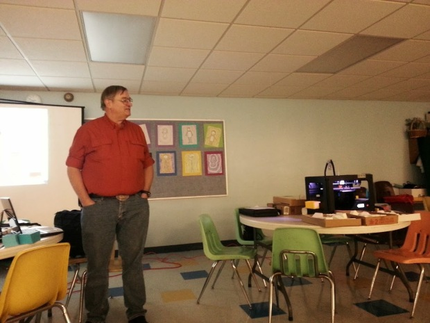 A man giving a presentation while standing next to a projector and a 3D printer.