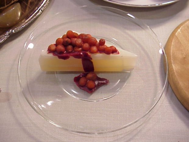 This looks like a slightly translucent slice of pale yellow cheesecake with small red cherries on top. It is actually a slice of rock with rocks on top.