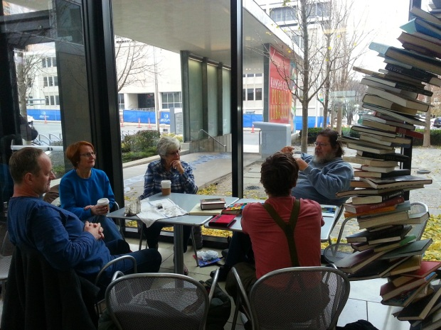Five people listening intently while sitting around a table littered with rocks and books about rocks. In the background there is a cool book sculpture and a sign reading