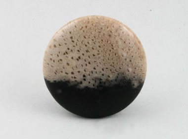 A perfectly round cabochon that is cream with dark brown speckles at the top two-thirds, and the bottom third is completely black.
