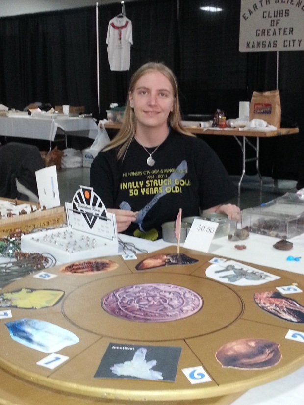 "A smiling young woman sitting behind a large wooden spinner with eight sections. She is wearing an ammonite necklace and a shirt proclaiming that the Kansas City Gem and Mineral Show ""finally struck gold"" and is 50 years old."