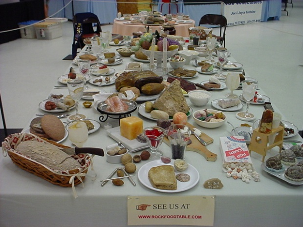 This looks like a huge spread of all sorts of food: bread baskets, muffins, popcorn, nuts, cheese, smoked salmon, fresh fruit, and more. It is actually all rocks.