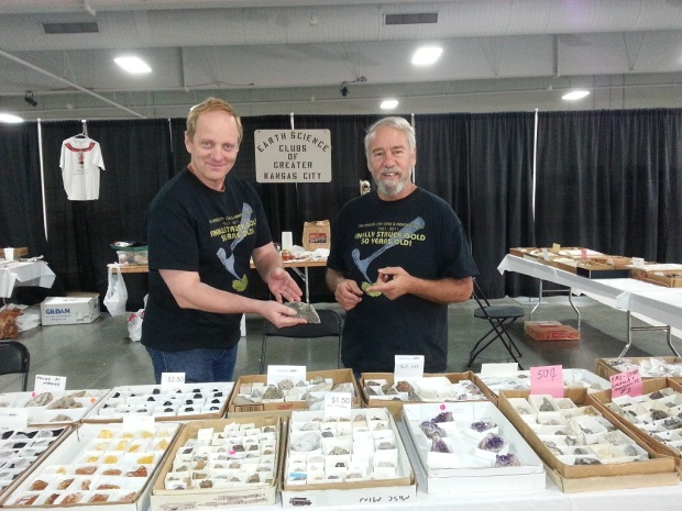 Two men holding rocks and standing in front of a table covered in boxes of colorful crystals. Behind them is a sign that reads,