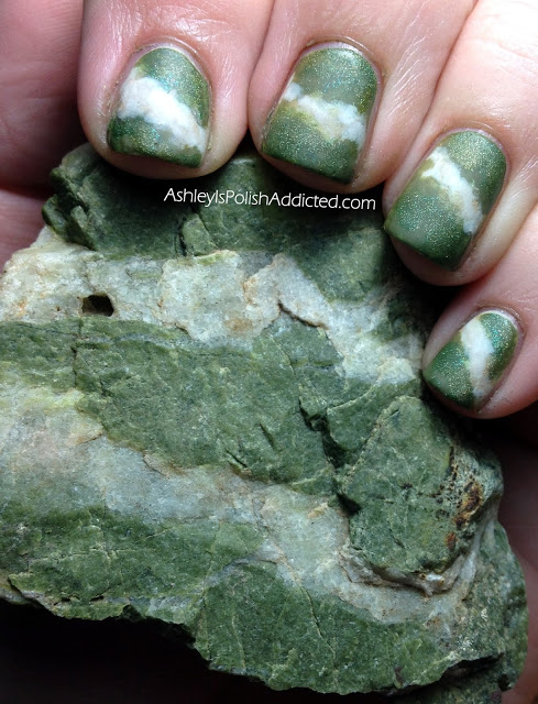 A hand with green and white banded fingernails that perfectly match the green and white banded rock it is holding.