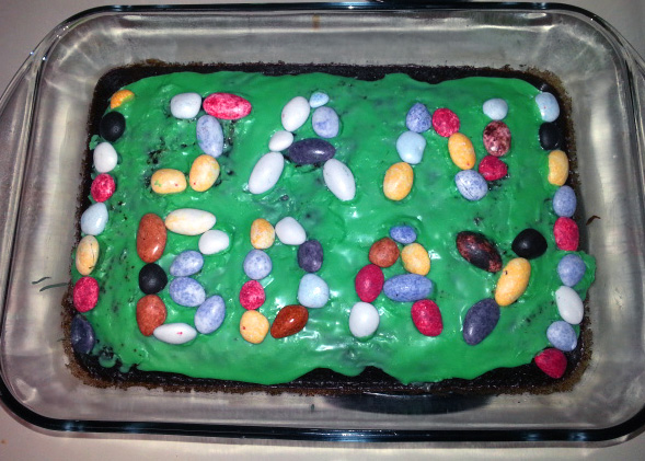 A chocolate cake with green icing and multicolored rocks spelling