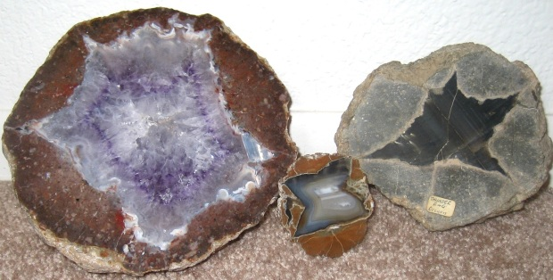 Three round geodes in small, medium, and large. The smallest one is a flat slab with a blue inside and brown outside. The medium one is a hemisphere that's black on the inside and gray on the outside. The largest one is a hemisphere that is purple amethyst crystals on the inside and brown on the outside.