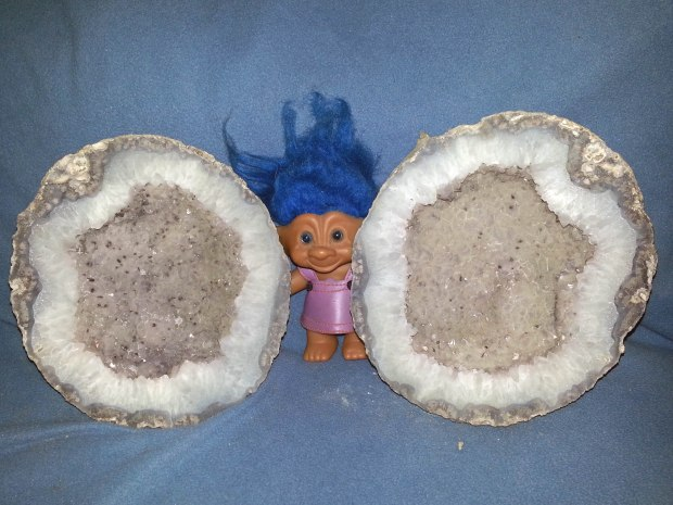 A troll doll with blue hair sitting in between two halves of a grayish-purple geode.