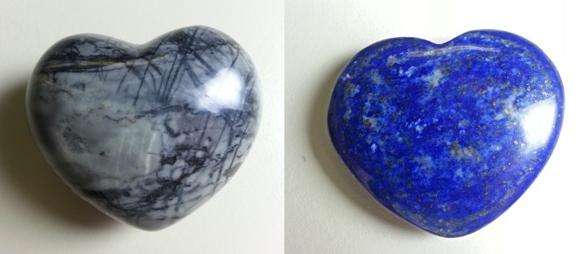 Two shiny stones carved into heart shapes. One is gray with black cross-hatched lines and the other is blue with small white swirls and gold sparkles.