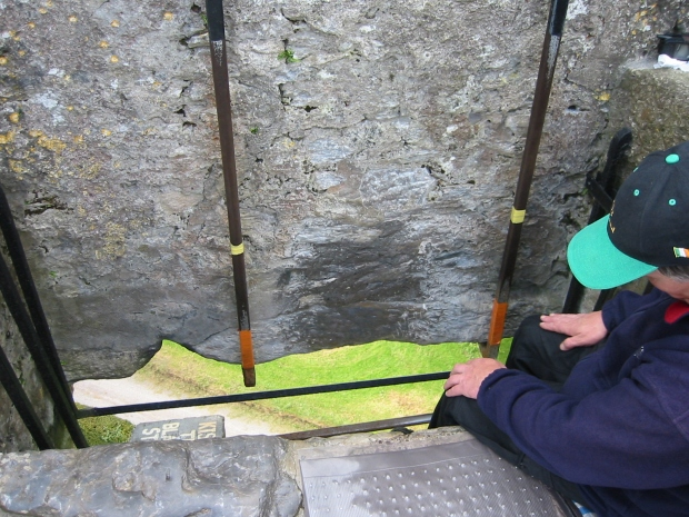 The Blarney Stone looks like a big gray stone with a metal railing attached. You can see the ground far below.