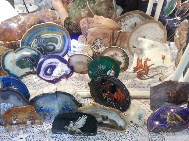 Colorful agate slabs with dragons, cats, penguins, and other creatures painted on them.