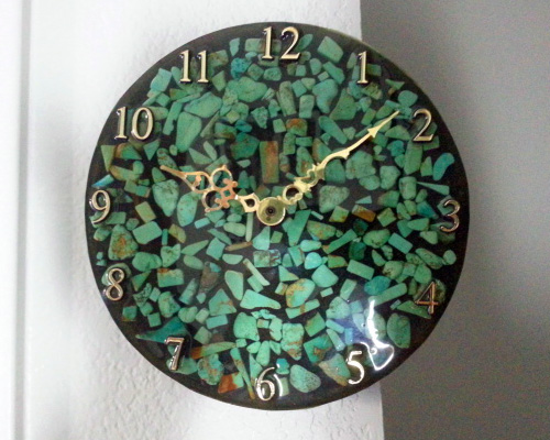 A round clock with green turquoise chips floating in resin on a black background. It has ornate gold hands and numbers that complement the gold flecks in the turquoise.