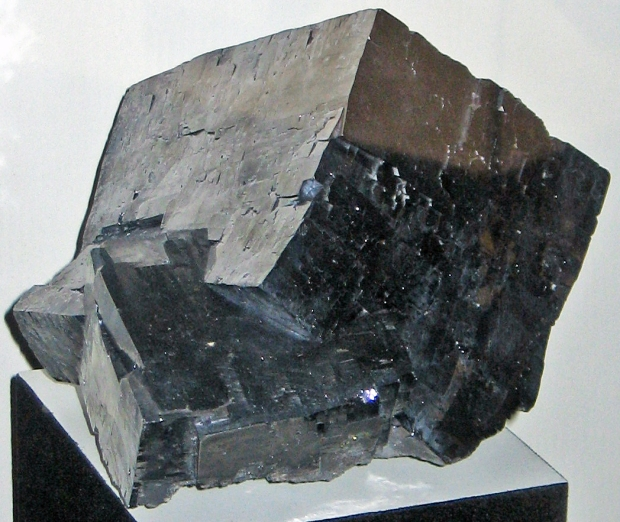 A huge shiny smooth silver-black cube on a display stand.