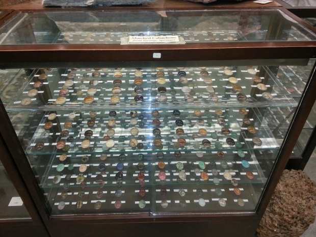 A display case full of hundreds of colorful round semiprecious stones.