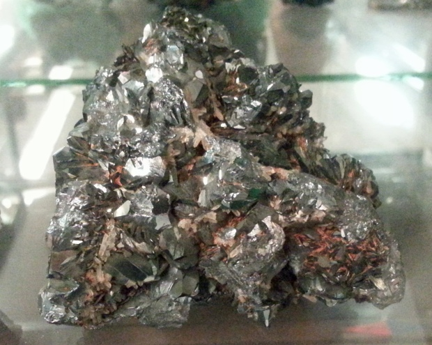 A rock that looks like a cluster of small gray bits of shiny steel with spots of red rust.