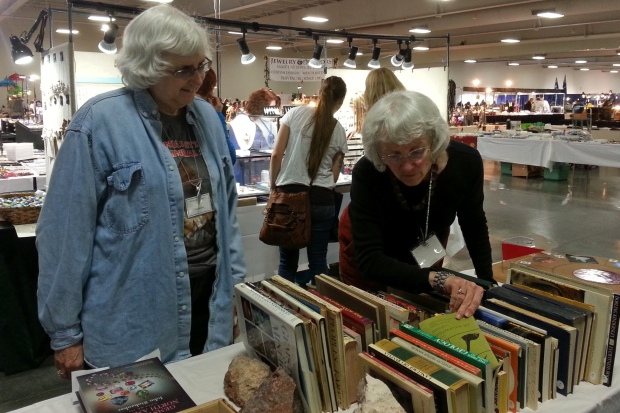 Two women looking at books about rock collecting.