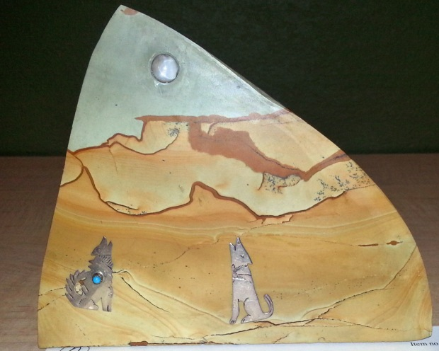 A landscape agate with coyotes and a moon added in copper