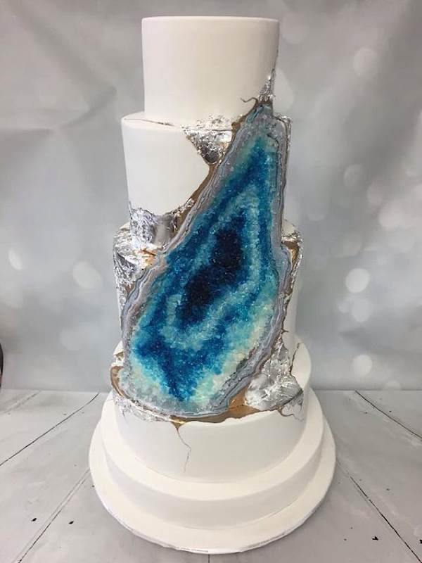 a white layered cake with a blue candy geode decoration