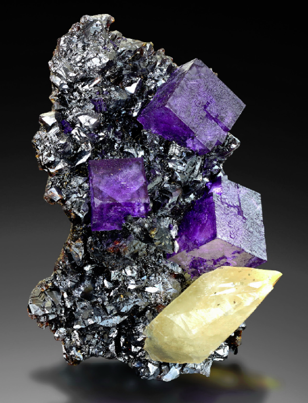 A silver sphalerite matrix with some purple fluorite crystals and a yellow calcite crystal on it.